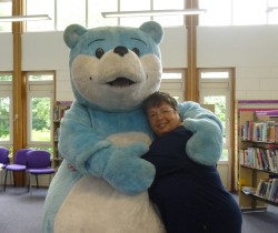 Kim A Howard cuddling the big blue Bookstart bear